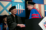 John Corigliano, a Grammy Award-winning composer, left, receives an honorary degree from the Rev. Dennis H. Holtschneider, C.M., president of DePaul, Saturday, June 10, 2017, during the DePaul University School of Music and The Theatre School commencement ceremony at the Rosemont Theatre in Rosemont, IL. (DePaul University/Jeff Carrion)