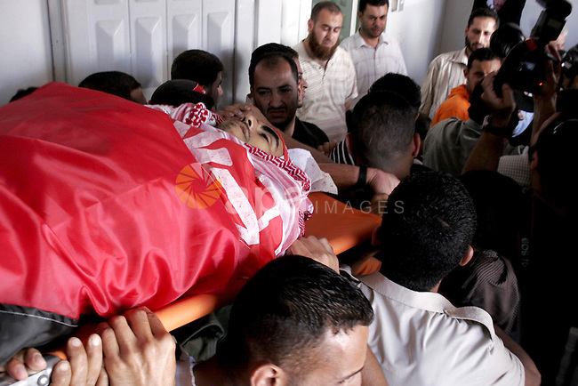 Palestinians mourn the body of Basaam Bedwan during his funeral in Gaza City on June 29, 2010, Bedwan was killed when an Israeli tank shell exploded near him. According to local media reports, one Palestinian was killed and three others were wounded. Photo by Yousef Deeb