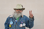 "Merrick, New York, USA. October 23, 2016. FRED S. CHANDLER, 66, of North Bellmore, wears political campaign buttons supporting Democratic presidential candidate Hillary Clinton, and holds two fingers up to make a Peace Sign or ""V for Victory"" sign, while attending rally to demand public water and stop New York American Water (NYAW) rate hike. On denim jacket were buttons for Hofstra University DEBATE 2016 - and ""So My Daughter Knows She Can Be President. Hillary 16"" - ""TRUMPBUSTERS"" - ""CLINTON KAINE 16"" - and Monopoly Man character with ""NEVER TRUMP"" text."