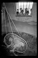 Chinese children look at a toddler sleeping in a hanging basket at a nursery set up to take care of children of farmers at a village in Guangdong province, China, 1988.