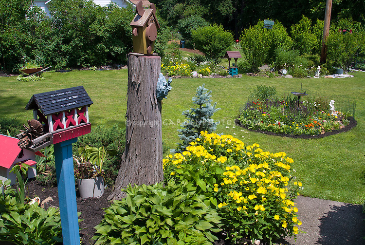 Bird feeders, ornaments, circular beds, colorful flowers, lawn grass, wheelbarrow planter, cute backyard garden