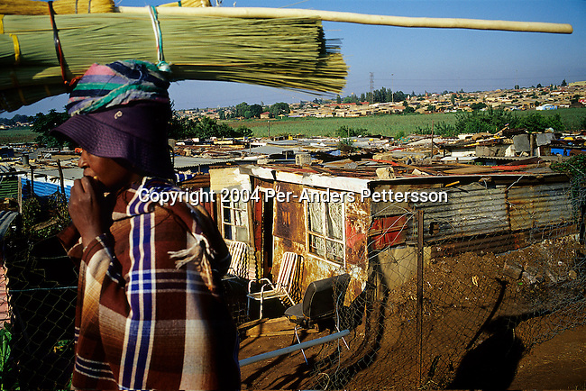 SOWETO, SOUTH AFRICA FEBRUARY 28: An unidentified woman walks past an area with shacks on March 28, 2004 in Chris Hani Squatter camp, in Soweto, Johannesburg, South Africa. Thousands of people still live in dire conditions without water or electricity, even after a black run government since 1994. South Africa?s largest township and it was founded about one hundred years to make housing available for black people south west of downtown Johannesburg. The estimated population is between 2-3 million. Many key events during the Apartheid struggle unfolded here, and the most known is the student uprisings in June 1976, where thousands of students took to the streets to protest after being forced to study the Afrikaans language at school. Soweto today is a mix of old housing and newly constructed townhouses. A new hungry black middle-class is growing steadily. Many residents work in Johannesburg but the last years many shopping malls have been built, and people are starting to spend their money in Soweto. .(Photo by Per-Anders Pettersson/Getty Images).