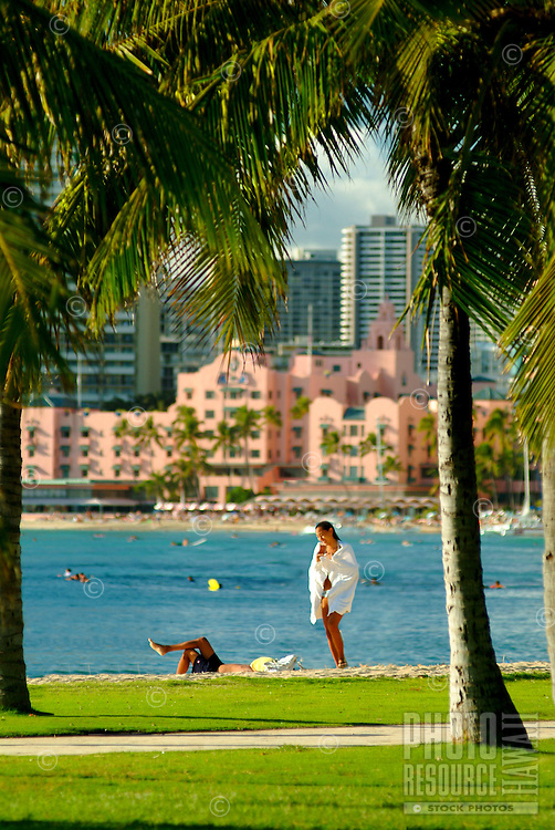 "A woman strolls along a palm tree lined path off  Waikiki Beach with the blue ocean and the Royal Hawaiian Hotel, or """"pink palace"""" in the background."
