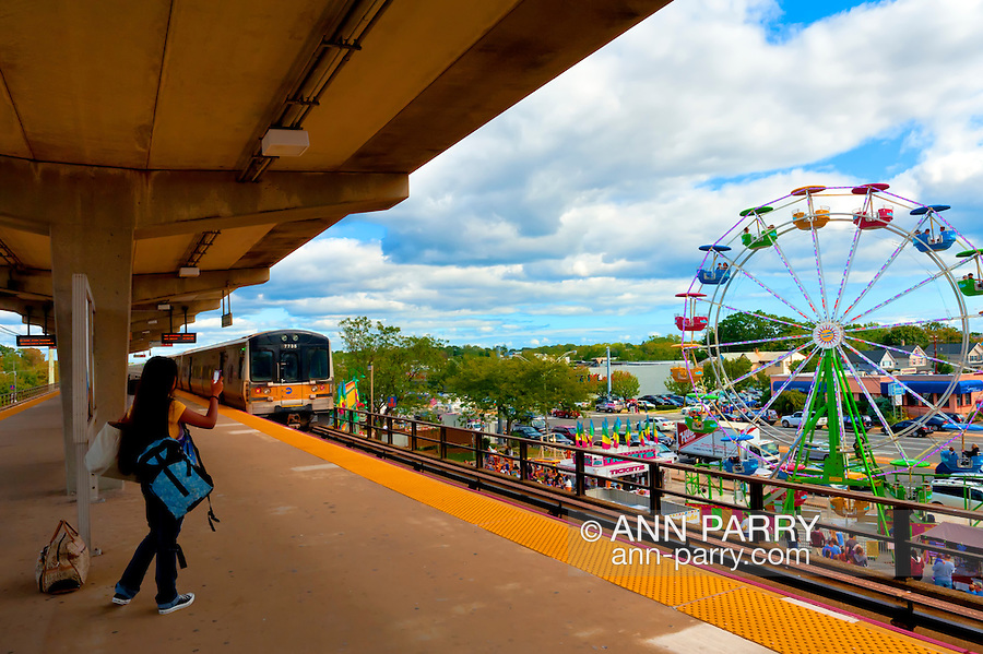 On elevated platform of Long Island Railroad, with LIRR train leaving, girl taking photo of Bellmore Fair carnival rides, including ferris wheel, New York, September 18, 2011.
