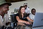 Cheetah (Acinonyx jubatus) biologist, Xia Stevens, reviewing photographs from lodge guides, Moses Mwale, Mullah Maipenzi, and Joseph Sandala, to identify individual cheetahs, Kafue National Park, Zambia