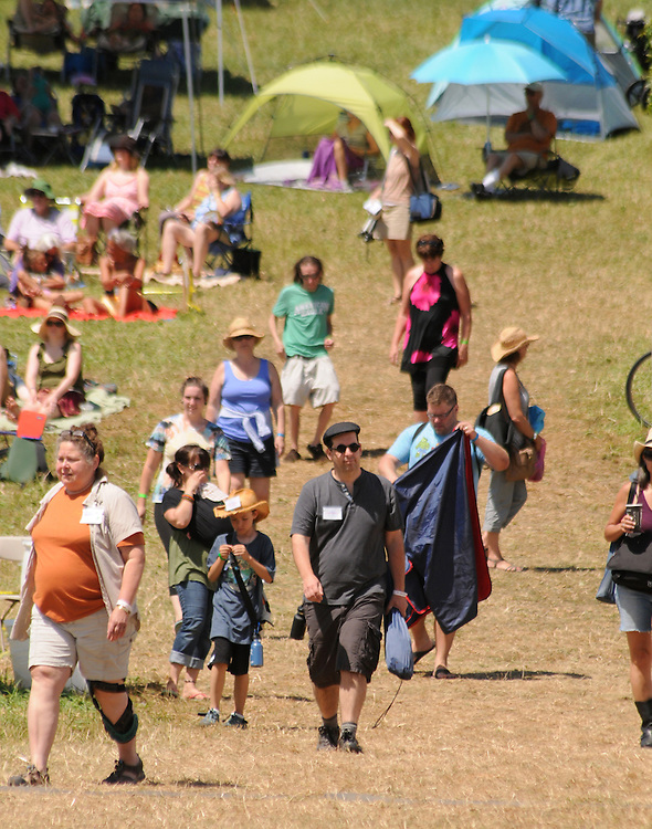 People coming from the camping area in the morning at the Falcon Ridge Folk Festival, held on Dodd's Farm in Hillsdale, NY on Sunday, August 2, 2015. Photo by Jim Peppler. Copyright Jim Peppler 2015.