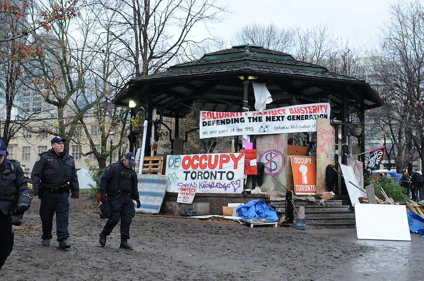 November 23, 2011, Toronto Police deployed in significant numbers this morning, beginning the process of evicting the Occupy Toronto tent camp from St. James Park.  Here, three Police Constables walk past the boarded up band shell.