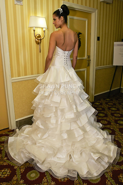 Model poses in a pearl white silk mocado ruffle layered gown; from Karen Sabag Spring 2012 Bridal collection, during  Couture: New York Bridal Fashion Week 2012