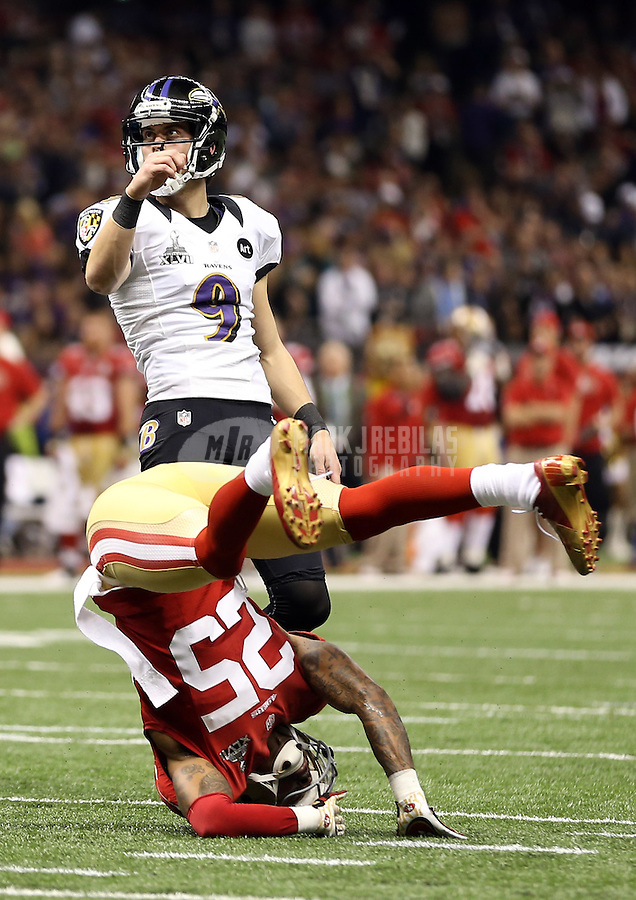Feb 3, 2013; New Orleans, LA, USA; Baltimore Ravens kicker Justin Tucker (9) kicks a point after touchdown as San Francisco 49ers cornerback Tarell Brown (25) rolls over while trying to block it in the second quarter in Super Bowl XLVII at the Mercedes-Benz Superdome. Mandatory Credit: Mark J. Rebilas-