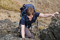 Female hiker climbs steep ridge to summit of Bla Bheinn, Black Cuillin mountains, Isle of Skye, Scotland