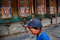 A boy walks past Tibetan Buddhist prayer wheels on the kora prayer path around the Labrang Monastery in Xiahe, Gansu, China. Xiahe, home of the Labrang Monastery, is an important site for Tibetan Buddhists.  The population of the town is divided between ethnic Tibetans, Muslims, and Han Chinese.