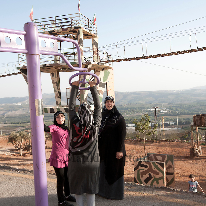 Lebanese family playing in the park. During his first state visit to Lebanon in October 2010  Iranian President Dr. Ahmadinejad went to Bint Jbeil, a village at Israel-Lebanon border. Its the place where fierce battles between Hizbullah and the Jewish Army were fought. In addition to praising the courage of the Lebanese nation against the powerful enemy supported by the US, France, Germany and Britain  Dr. ahmadinejad also performed the inauguration ceremony of the Iran Park at Maroun al-Ras border area where streets are named after the Iranian cities...The Iranian government has funded and designed a lush park near the site of the battle, on the mountainside directly overlooking Israel. In the parking, visitors can stand at an observation point beside an Iranian flag fluttering in the wind, and look directly down at the Israeli hamlets of Avivim and Yiron.