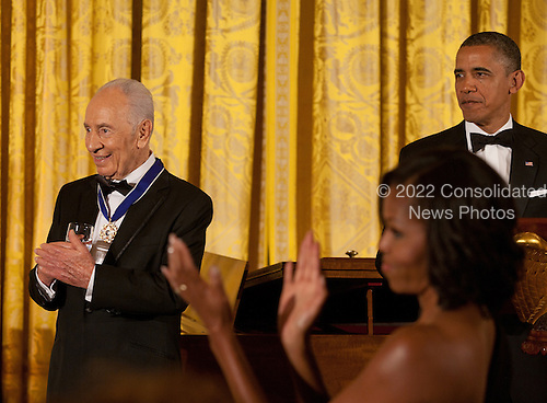 President Shimon Peres  of Israel (left) and first lady Michelle Obama applaud as United States President Barack Obama recognizes former President Bill Clinton (not shown) following the presentation to Peres of the Presidential Medal of Freedom during a dinner in his honor in the East Room of the White House in Washington, D.C. on Wednesday, June 13, 2012..Credit: Martin Simon / Pool via CNP