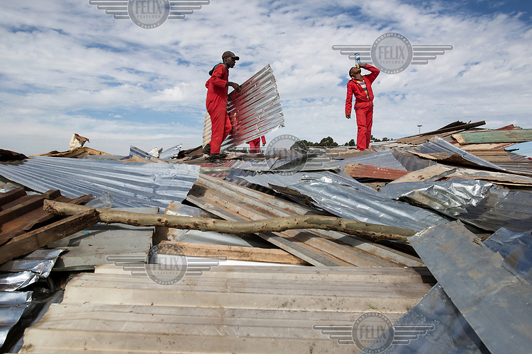 After demolishing shacks, the metal sheeting used for walls and roofing are stacked up for removal at the Skoonplaas informal settlement.