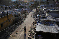 Residents walk past the debris left by a Scud missile in the Tariq Al-Bab neighborhood of Aleppo. ..At least three Russian-made Scud missiles landed in Aleppo's Al-Hamra, Tariq Al-Bab and Jabal Badro/Hanano neighborhoods since the beginning of 2013. All three landed in heavily populated areas located in the rebel-controlled region of the city. Residents claim there are no rebel fighters living in these neighborhoods. The death toll is past 100, by reports, from at least two incidents on the week of Feb. 18, and  a total of 123 casualties according to Human Rights Watch.