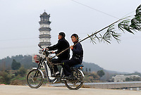 Chinese man drives an electric motor bike with a lady in Yifeng, Jiangxi province, China. .