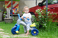A one-year-old local boy plays on a tricycle in front of a red car outside his home on the Big Island.