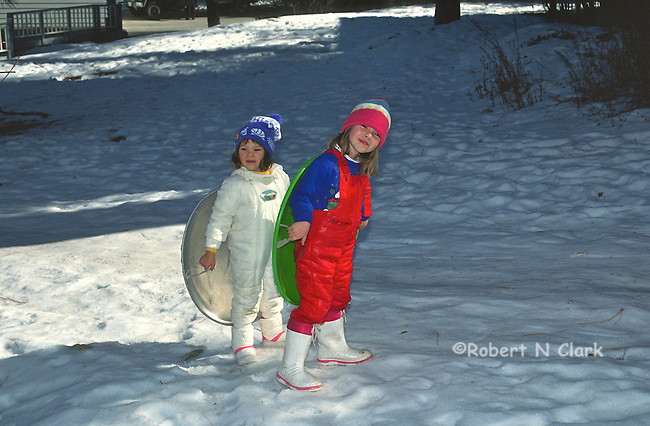 Two girl in snow with snow saucers