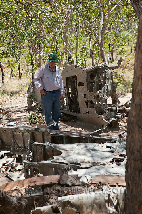 Tourist at the wreckage of a World War II aircraft on Horn Island.  The island was a strategic outpost during WWII and was bombed numerous times by the Japanese.  Horn Island, Torres Strait Islands, Queensland, Australia