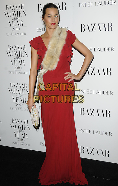 YASMIN LE BON .Harper's Bazaar Women of the Year Awards at One Mayfair, London, England, UK. .November 1st 2010.full length red maxi dress beige fur sash white clutch bag ruffle ruffles hair up cream hand on hip.CAP/CAN.©Can Nguyen/Capital Pictures.