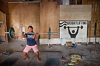Carisma, a young girl practicing weightlifting after school.   Nauru's Weightlifting Gym in Aiwo District (Aiwo's Boys Gym). Girls and boys train here every day starting at 5pm. Nauru's weightlifting champions (including the President of Nauru) have won several gold medals at the Commonwealth Games. Weightlifting is the pride of the nation..Although Nauru is the world's fattest country, with 94% of its population being overweight, teenagers are very fit and sportive. Amongst the favorite sports are weightlifting, Aussie Rule football (a kind of Rugby) and boxing. ..Nauru, officially the Republic of Nauru is an island nation in Micronesia in the South Pacific.  Nauru was declared independent in 1968 and it is the world's smallest independent republic, covering just 21 square kilometers..Nauru is a phosphate rock island and its economy depends almost entirely on the phosphate deposits that originate from the droppings of sea birds. Following its exploitation it briefly boasted the highest per-capita income enjoyed by any sovereign state in the world during the late 1960s and early 1970s..In the 1990s, when the phosphate reserves were partly exhausted