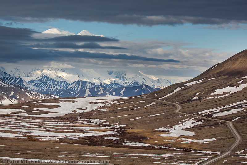 Denali mostly obscured by clouds as viewed from Stoney Dome, the Denali Park road weaves through the tundra. Denali National Park, Alaska.