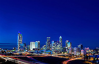 Downtown buildings in the Charlotte NC skyline take on a brilliant glow as they reflect the rising sun. Buildings shown in photo include the Duke Energy headquarters (far left), Wells Fargo buildings (middle), Bank of America tower (tallest on right) and Hearst Tower (tall far right).<br /> <br /> Charlotte Photographer - PatrickSchneiderPhoto.com