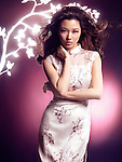 Fashion photo of a beautiful young asian woman wearing a summer dress with blooming cherry tree branch behind her