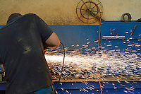 Man cutting steel with grinder at factory