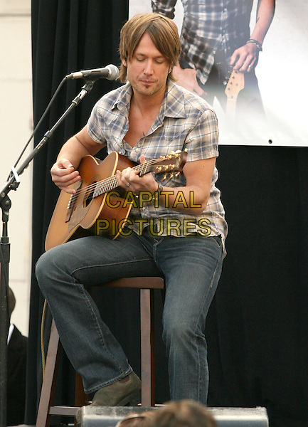 KEITH URBAN.is joined by Verizon Wireless and Samsung Mobile as he makes an in-store appearance for his fans at the Verizon Wireless store in Pasadena, California, USA, November 21st 2009                                                                   .full half foot length music concert gig live on stage grey gray brown plaid checked check shirt jeans sitting microphone  playing tattoo bracelets guitar .CAP/RKE/DVS.©DVS/RockinExposures/Capital Pictures