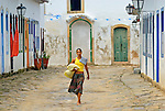 Local brazilian woman walking through the historic center; Paraty, Espirito Santo, Brazil. The beautiful colonial town of Paraty has been a UNESCO World Heritage Site since 1958. --- No signed releases available.