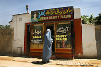 A woman in a burqa stops to look inside a newly opened beauty parlour. Kabul,Afghanistan,Asia.