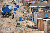 A Peruvian water distribution worker with a hose splashes drinking water from a truck into a plastic barrel on the dusty hillside of Pachacútec, a desert suburb of Lima, Peru, 21 January 2015. Although Latin America (as a whole) is blessed with an abundance of fresh water, having 20% of global water resources in the the Amazon Basin and the highest annual rainfall of any region in the world, an estimated 50-70 million Latin Americans (one-tenth of the continent's population) lack access to safe water and 100 million people have no access to any safe sanitation. Complicated geographical conditions (mainly on the Pacific coast), unregulated industrialization (causing environmental pollution) and massive urban poverty, combined with deep social inequality, have caused a severe water supply shortage in many Latin American regions.