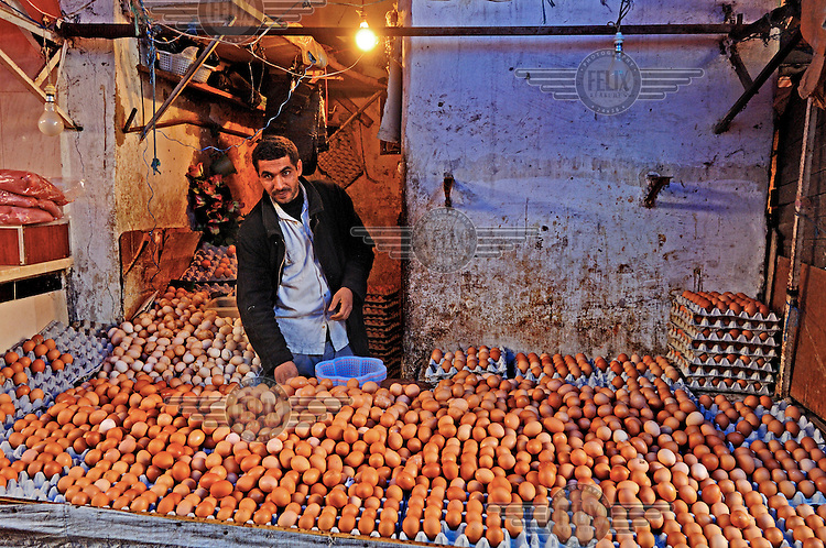 A man surrounded by hundreds of eggs being sold on a stall in the Medina.