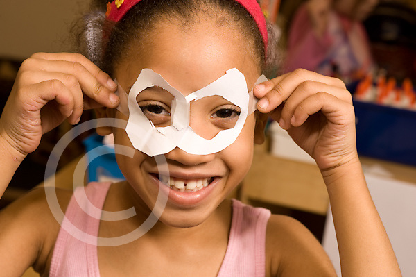 Education elementary Kindergarten portrait of girl peeking through paper mask she made herself horizontal
