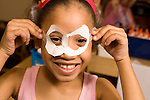 Education elementary Kindergarten portrait of girl peeking through paper mask she made herself horizontal