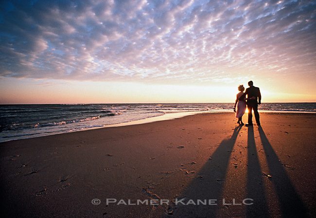 Senior Couple in formal attire On Beach At  Sunset