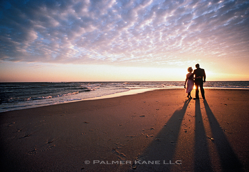 Senior Couple in formal attire On Beach At  Sunset