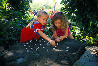 Two young girls playing konane (Hawaiian checkers) Sea life park, Oahu