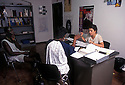 Elena Bartoli in charge of the Assistance Center for Immigrants, speaks with Ghananian immigrants at his office in Nonantola, June, 1996...2006 Nonantola (Modena), centro assistenza immigrati del Comune;La responsabile Elena Bartoli con due immigrati ghanesi.