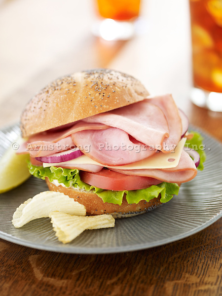 A sandwich with sliced ham, tomatoes, lettuce, and mayonnaise on a poppy seed kaiser roll. On a plate with potato chips and pickle, with a glass of iced tea in the background.