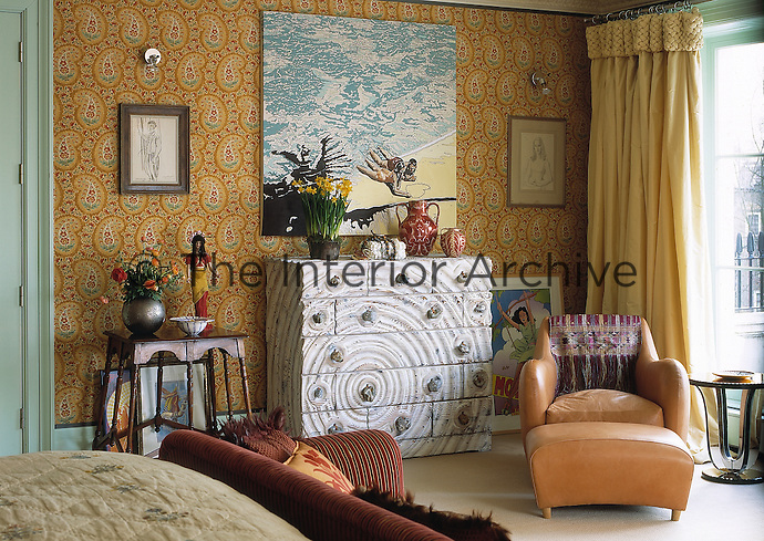 A bedroom with an eclectic mix of furniture styles and paisley pattern yellow wallpaper. A leather armchair and ottoman stand next to a contemporary chest of drawers,