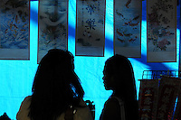 Mesa, Arizona. November 4, 2012 - The silhouettes of two women are seen inside this booth where vendors offered typical Asian artwork and products. This scene was captured during the 18th Annual Asian Festival 2012 that took place at the Mesa Arts Center in Mesa, Arizona. In Arizona, Asian-Americans celebrated a colorful festival where their rich culture was admired and their growing presence affirmed. Asian-Americans are now the United States fastest-growing racial group, the best-educated and highest-earning workers. Photo by Eduardo Barraza © 2012