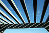 Converging lines of a wooden pergola against a blue sky.