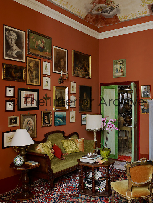 The terracotta colour walls of the study are the perfect backdrop for a collection of assorted artwork