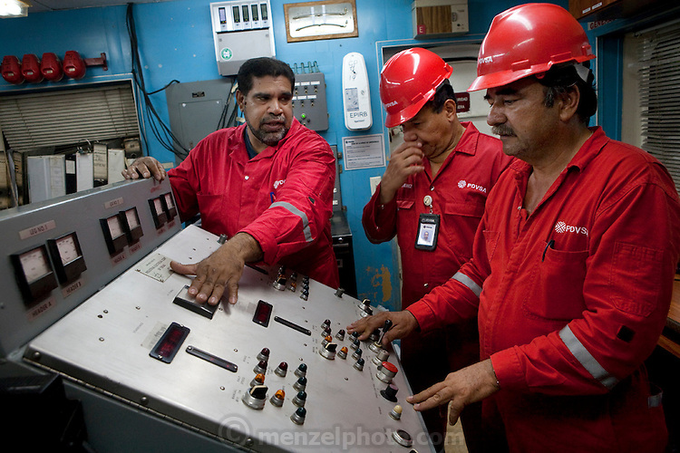"Oswaldo Gutierrez (center), Chief of the PDVSA Oil Platform GP 19 in Lake Maracaibo, Venezuela, monitors operations with his colleagues on an oil rig. (From the book What I Eat: Around the World in 80 Diets.) The caloric value of his day's worth of food on a day in December was 6000 kcals. He is 52; 5'7"" and 220 pounds. Gutierrez works on the platform for seven days then is off at home for seven days.   While on the platform he runs on its helipad, practices karate, lifts weights, and jumps rope to keep fit. His food for the seven days comes from the platform cafeteria which, though plagued with cockroaches, turns out food choices that run from healthful to greasy-fried. Fresh squeezed orange juice is on the menu as well and Gutierrez drinks three liters of it a day himself. His diet changed about ten years ago when he decided that he'd rather be more fit than fat like many of his platform colleagues. PDVSA is the state oil company of Venezuela."