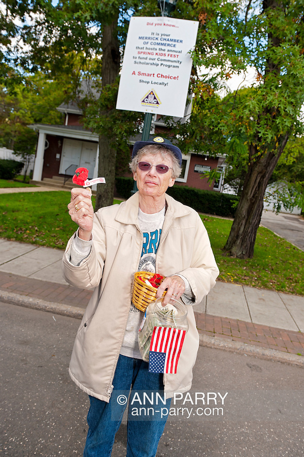 Auxiliary member of Merrick Post #1282 of American Legion holding up an artificial red poppy that people who make donations will get, at Merrick Street Fair in Merrick, New York, USA, on October 22, 2011