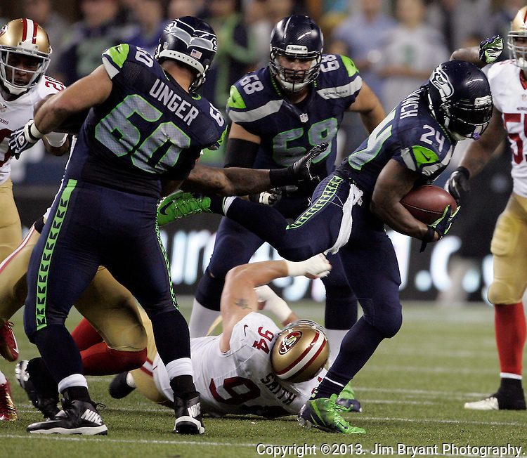 Seattle Seahawks  running back Marshawn Lynch (24) breaks a tackle by San Francisco 49ers  defensive tackle Justin Smith in the third quarter at CenturyLink Field in Seattle, Washington on September 15, 2013.  Lynch finished with 135 total yards, including 98 yards rushing yards on 28 carries, scored three touchdowns in the Seattle Seahawks 29-3 win over the 49ers .  ©2013. Jim Bryant Photo. ALL RIGHTS RESERVED.
