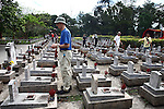 Veterans for Peace member Peter Moller says a prayer after placing incense on a grave at the Truong Son Martyrs Cemetery in Quang Tri province, Vietnam. The cemetery contains the graves of about 10,300 communist soldiers who died along the Ho Chi Minh Trail supply network into South Vietnam during the conflict from 1959 to 1975. Moller lost a brother in the war, and traveled to Vietnam in part to see the place where he died.  April 24, 2013.