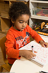 Education Preschool 4 year olds boy writing numbers with marker